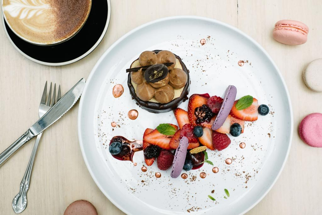 An aerial show of fruit and a small chocolate dessert on a white plate with a coffee in the corner above it