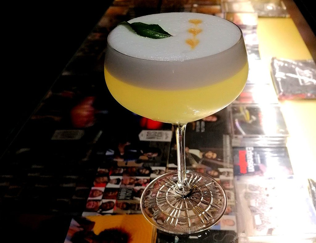 A cocktail with a foamy top on a wooden bench