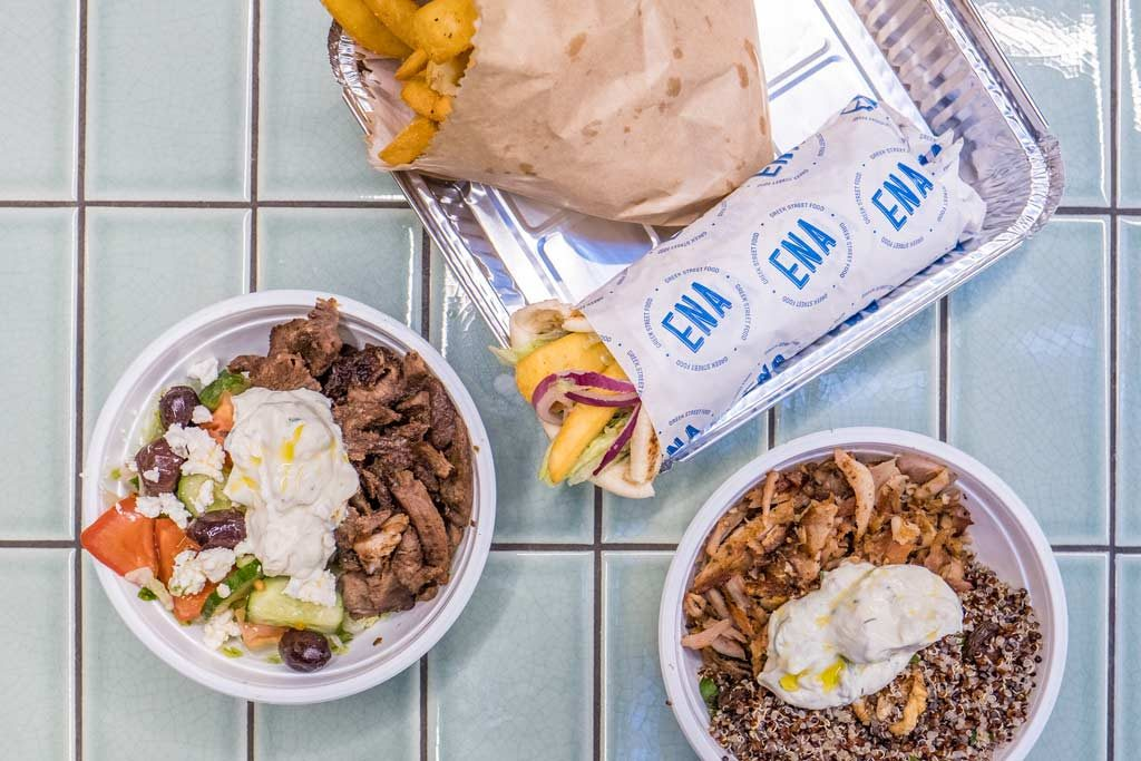 An aerial shot of Greek food in bowls and on a silver tray