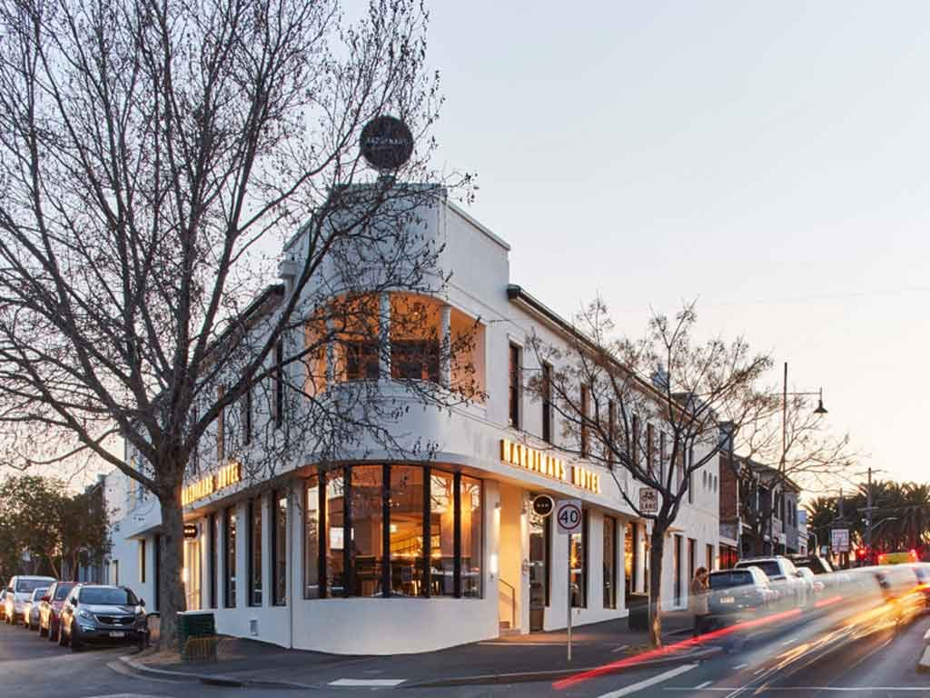 A large white pub on a street corner during a sunset