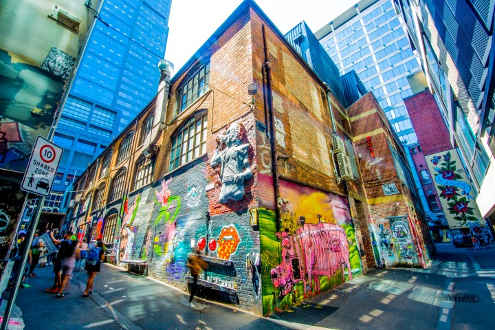 A sculpture of a man singing into a microphone on a wall covered with street art in a city laneway