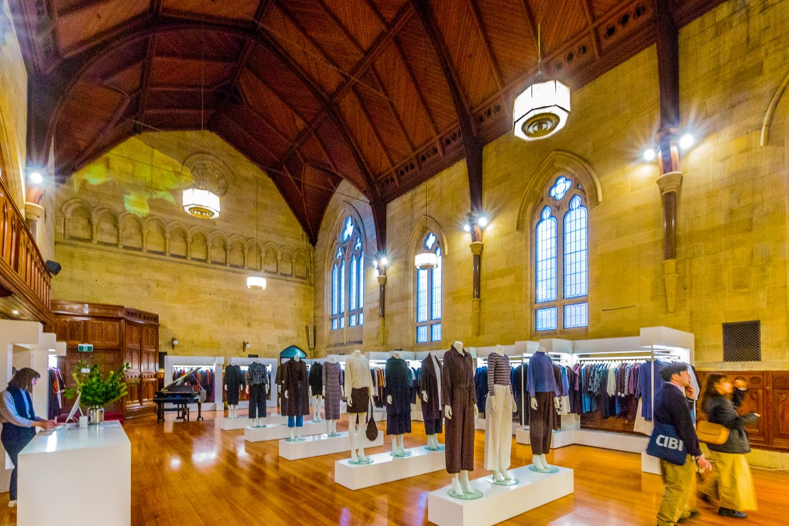 Mannequins and clothing displays in an elegant old hall with arched windows