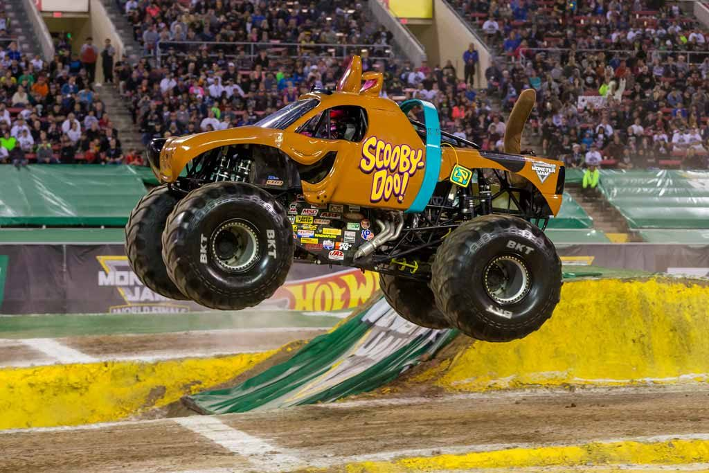 A monster truck designed to look like a cartoon dog jumping over a hurdle