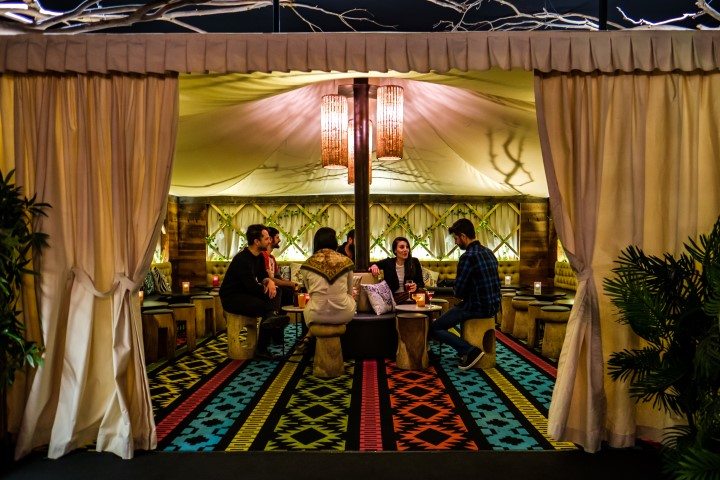 A group of people sitting on stools in a luxurious indoor tent