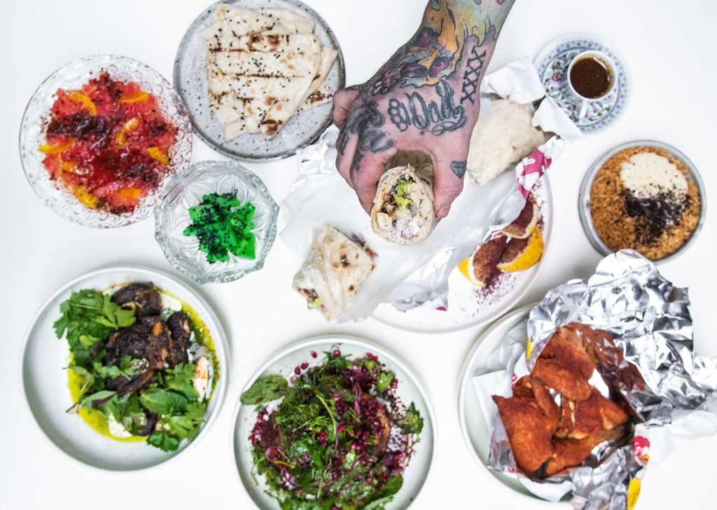 A man's tattooed hand reaching out over a table of food including salads, wraps and meat