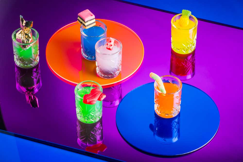Brightly coloured cocktail glasses with lolly garnishes on a colourful table top