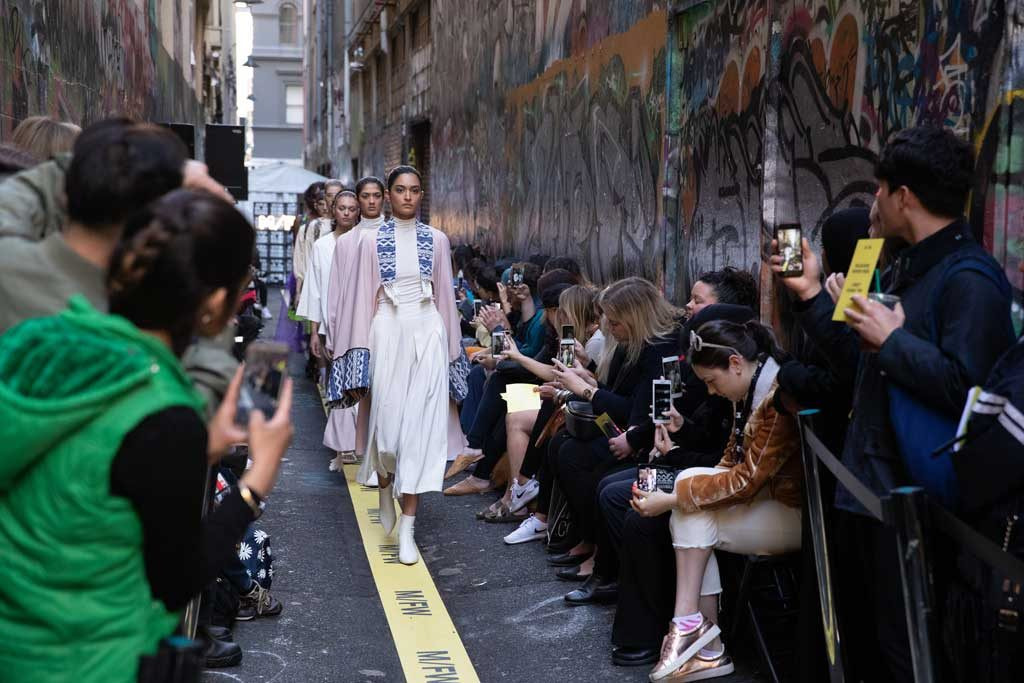 Models walking down a laneway in an outdoor runway with photographers along the sides