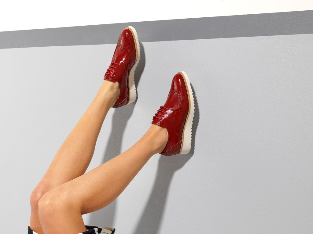 A woman wearing red shoes with her legs propped up on a wall