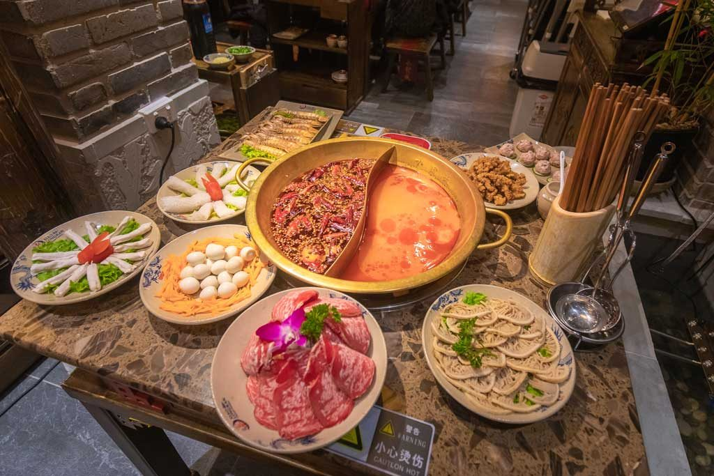 Hot pot on a table with plates of meat and vegetables around it