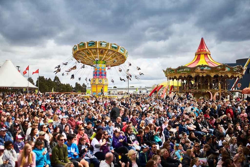 A carnival atmosphere with crowds around different rides and attractions