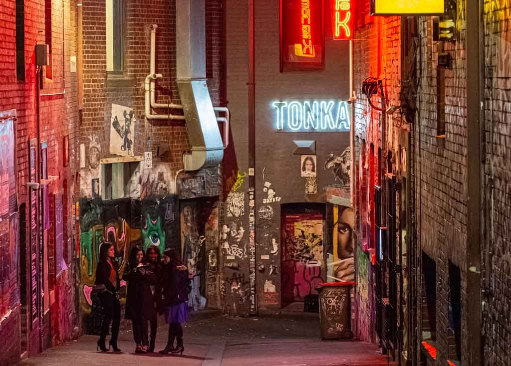 A night time scene in a neon lit alleyway