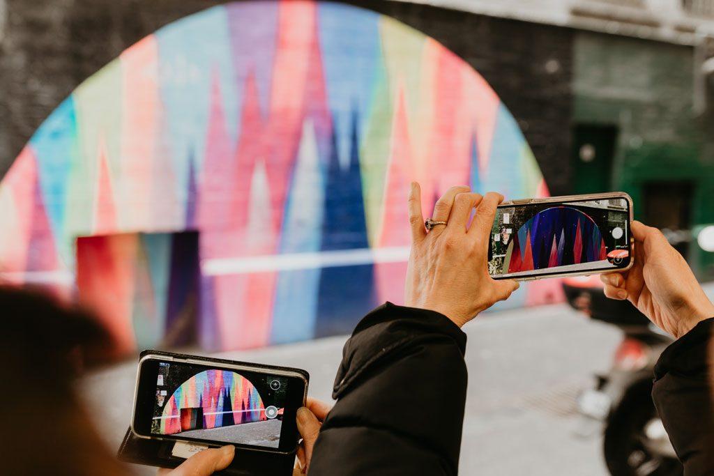 A semi circle shaped rainbow coloured artwork on a wall
