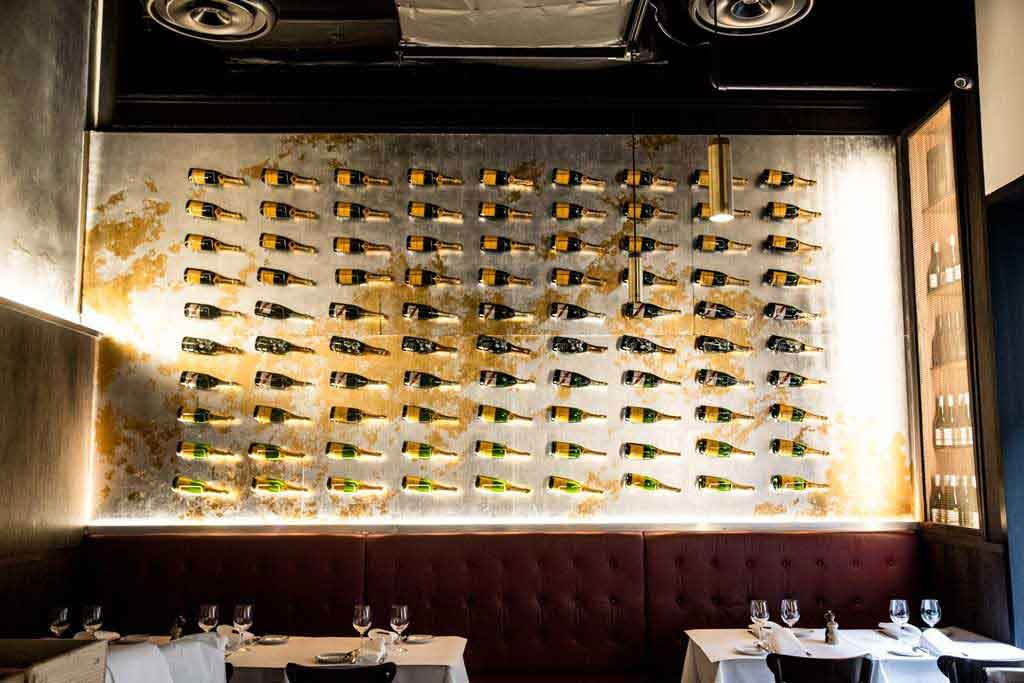 A large wall display of wine bottles suspended above tables in a restaurant
