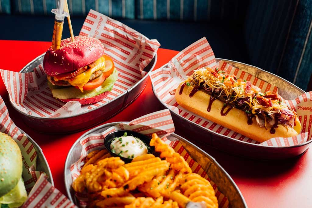 Hot dogs and burgers on metal trays