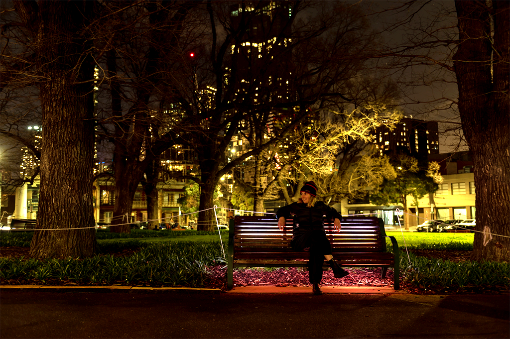 Woman sits on lit-up park bench at night with trees, park and city silhouetted in the background