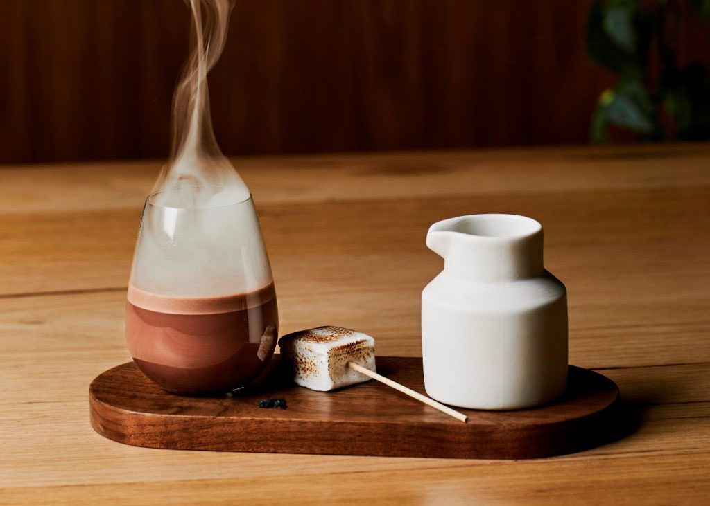 A hot chocolate on a wooden board with a white jug next to it and a toasted marshmallow beside it