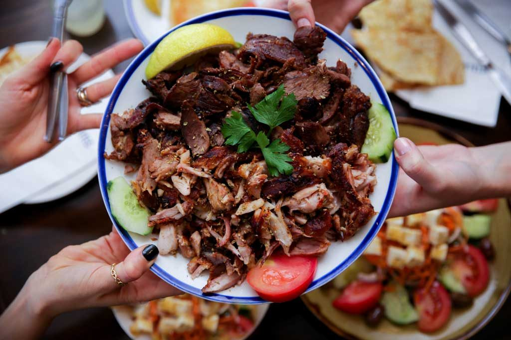 A plate of Greek meat being handed across a restaurant table