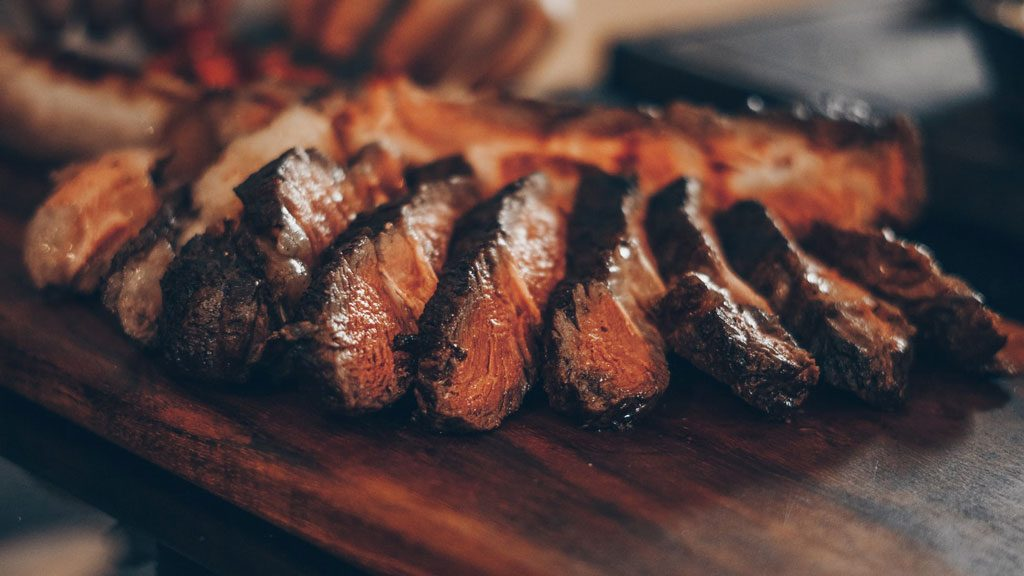 A rare steak chopped into slices on a wooden board