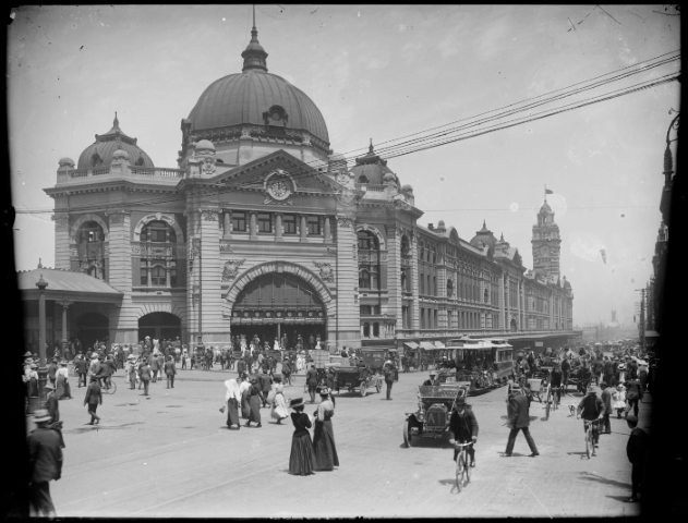 An old photograph of people walking and wearing old fashioned clothes and traffic outside a railway station.