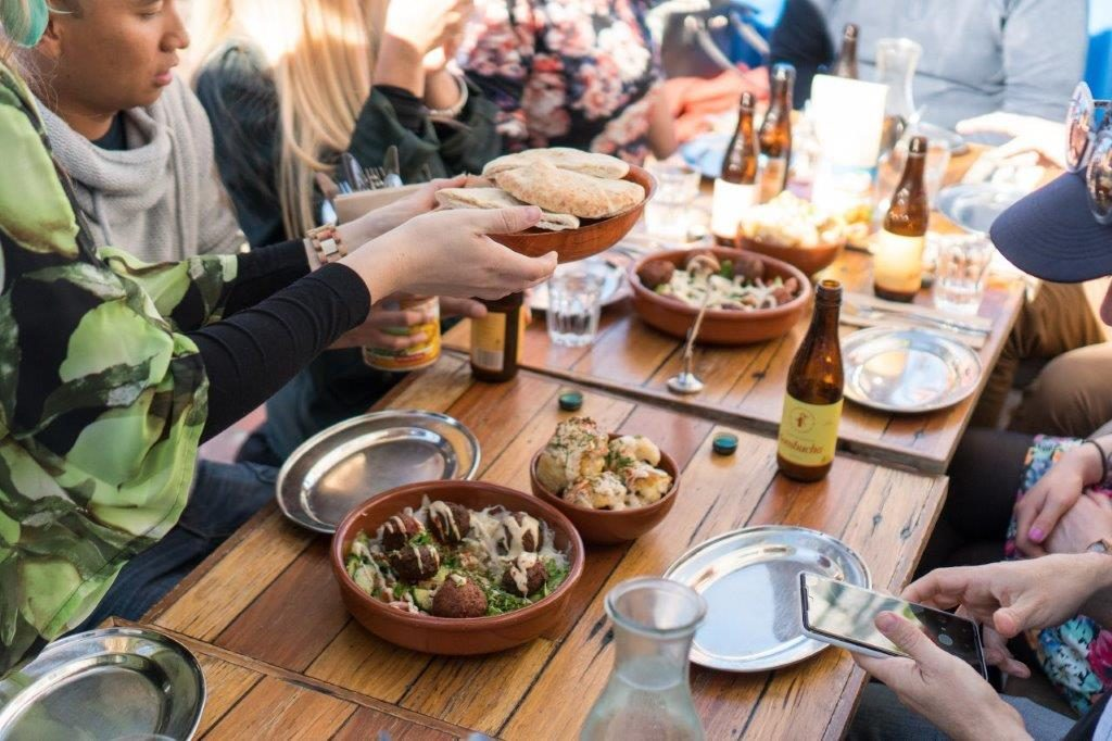 People sitting around a table sharing a selection of vegan food