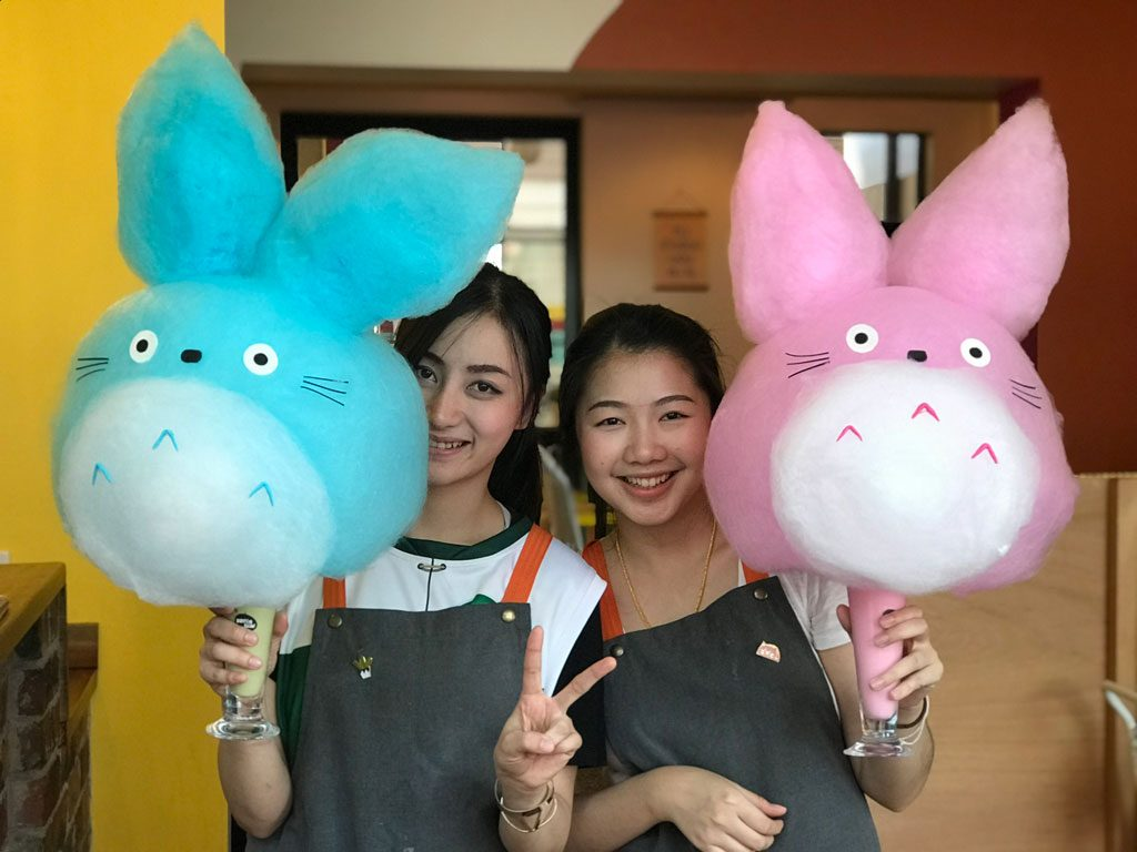 Two girls holding fairy floss shaped like cartoon characters