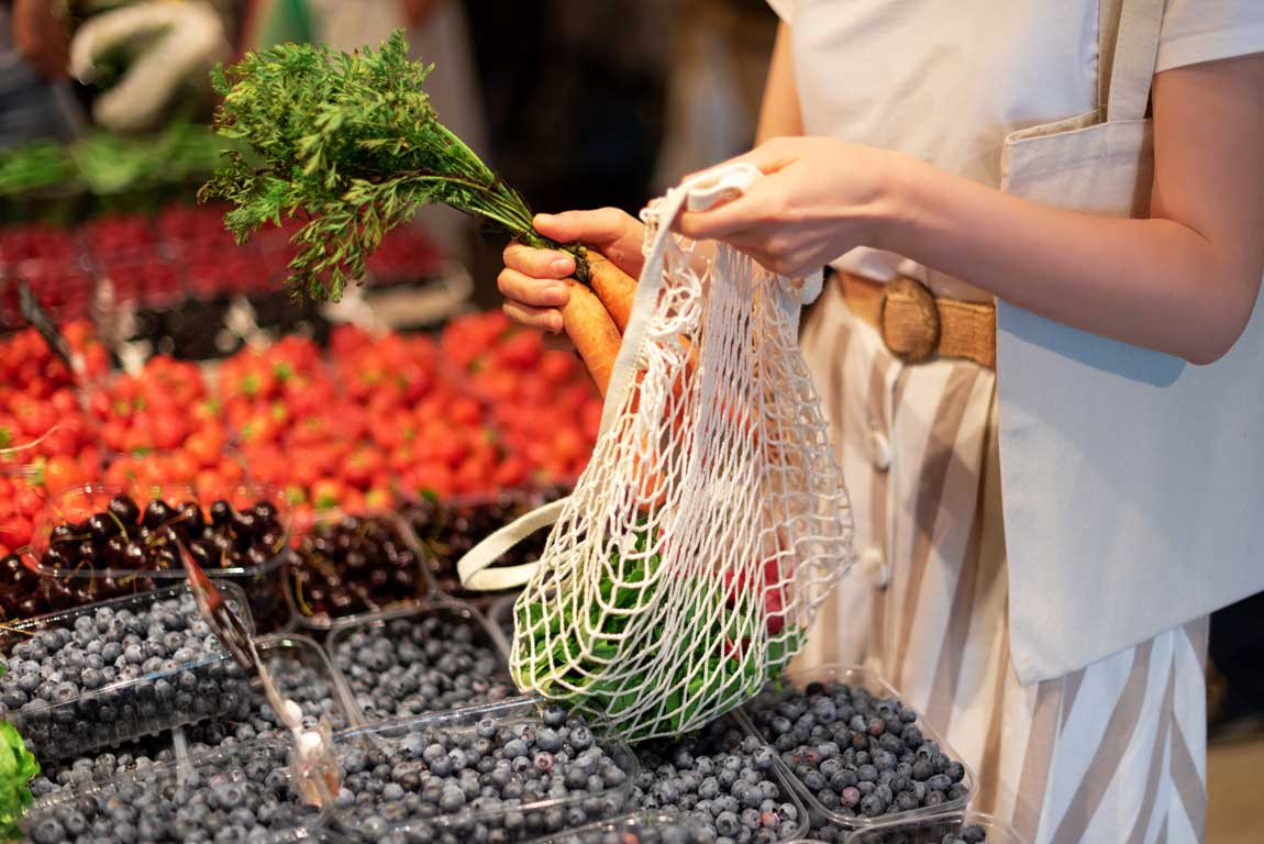 Hands putting carrots into a bag at a fresh produce stall