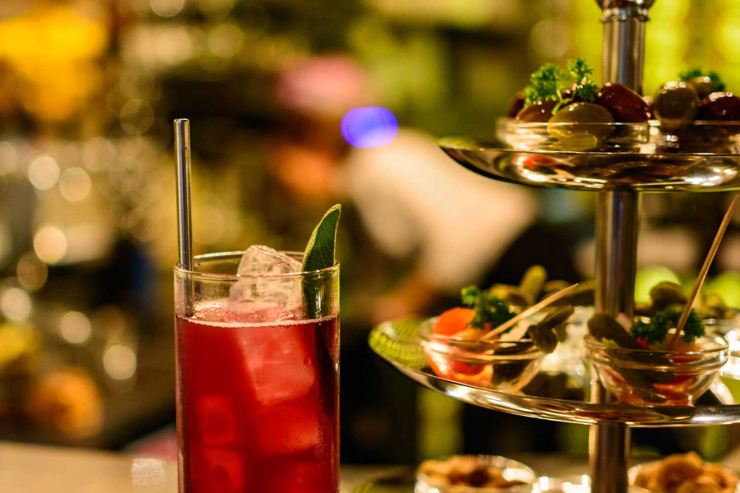 A cocktail with a metal straw next to a display of food