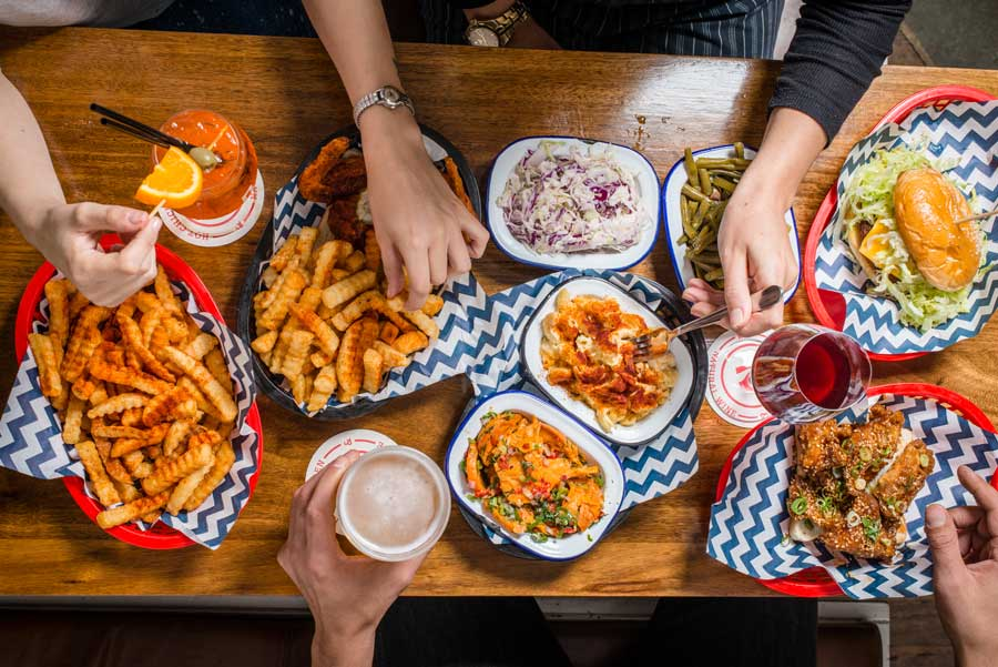 Several hands hovering over a huge feast of fried food