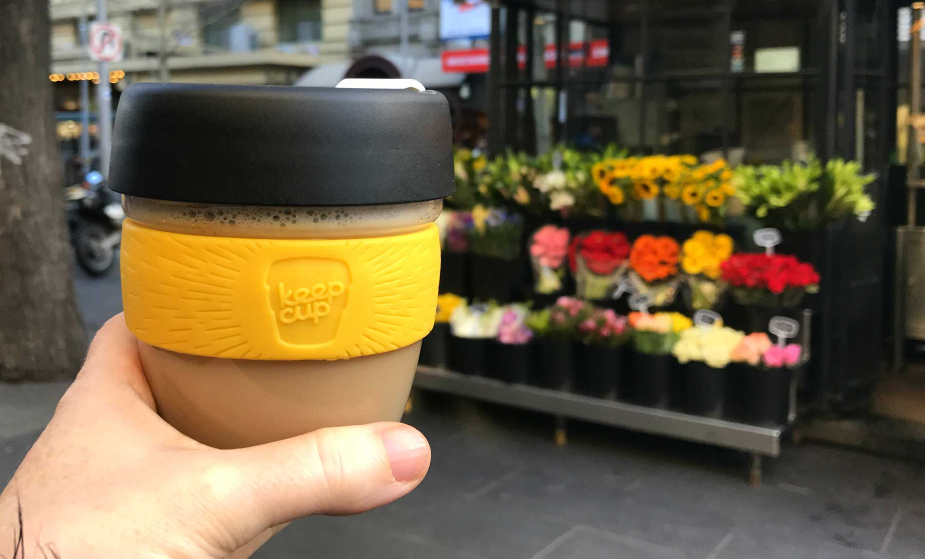 A hand holding a reusable coffee cup with a flower stall in the background