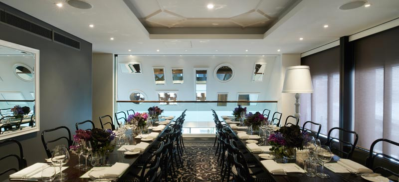 A modern, intimate dining room with long tables, and mirrors on the walls.