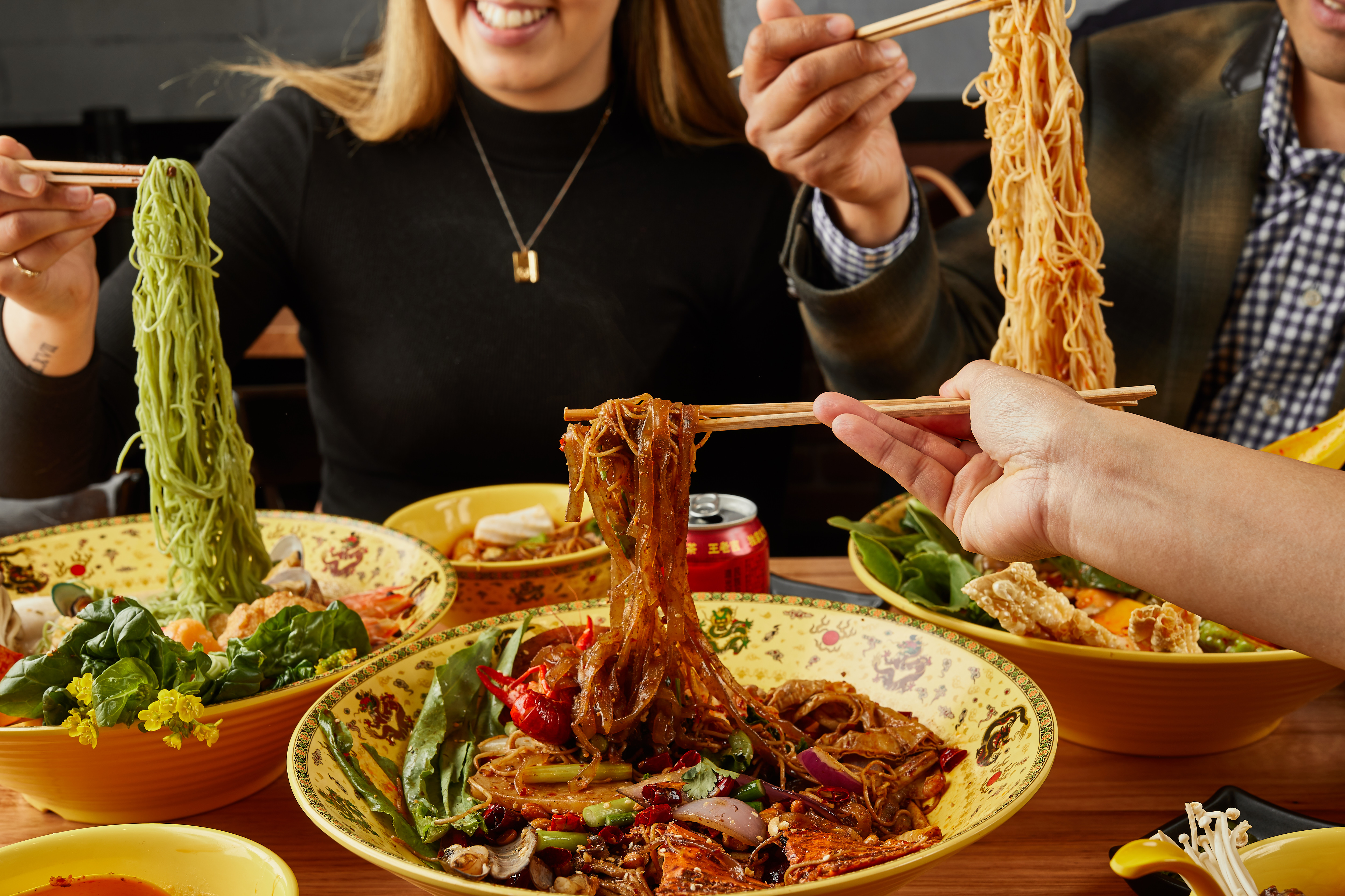 three sets of chopsticks picking up noodles in three bowls of soup at a table