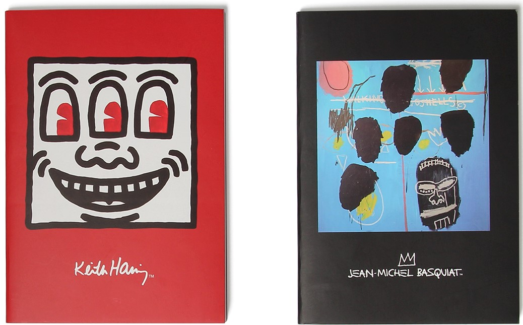 A red notebook with artwork of a cartoon square smiley face by artist Keith haring and Black note book with artwork by Basquiat on cover.