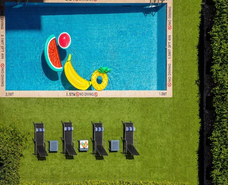A blue pool next to green grass and sun loungers. There are colour pool toys in the pool including a watermelon and banana