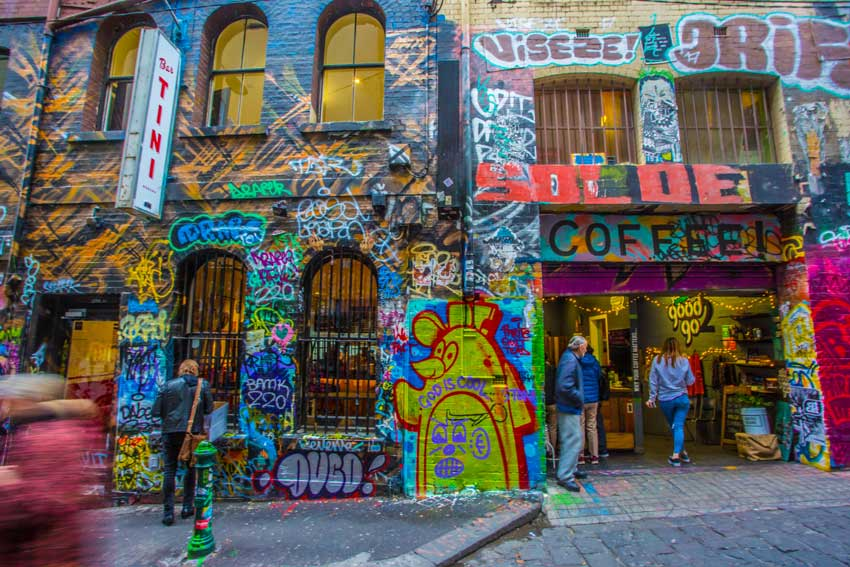 People standing outside a cafe in a street art covered laneway