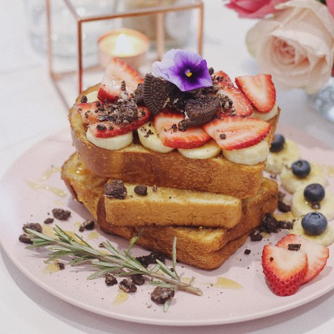 A stack of toast on a plate with berries and flowers on top