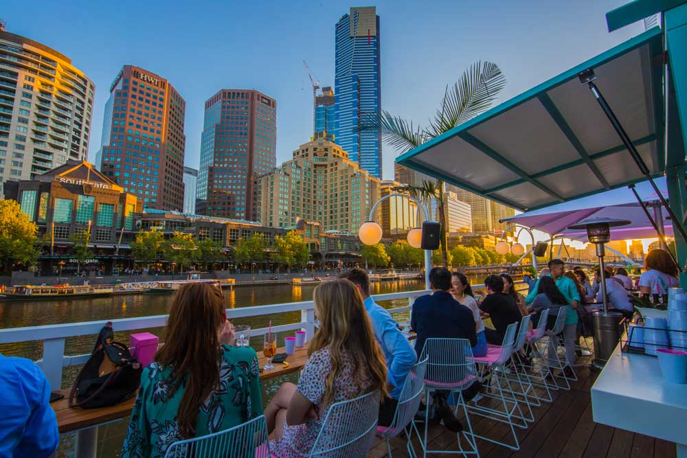 A group of people sitting in at an outdoor bar overlooking the river and the city skyline at sunset