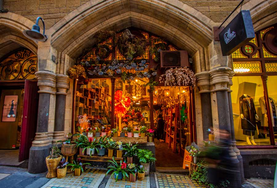 The window and entrance to a florist shop surrounded by flowers in an old church building