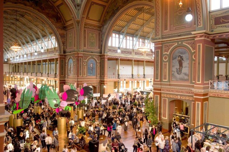 A birds eye view photo of a big hall filled with crowds exploring many different stalls.