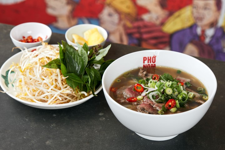 A plate of bean sprouts, a bowl of chillis, a bowl of lemons and a bowl of soup with beef, chillis and spring onions on top