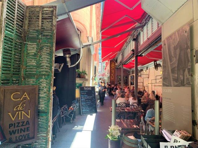 A city laneway with restaurant sign in foreground and people at tables sitting underneath red awnings