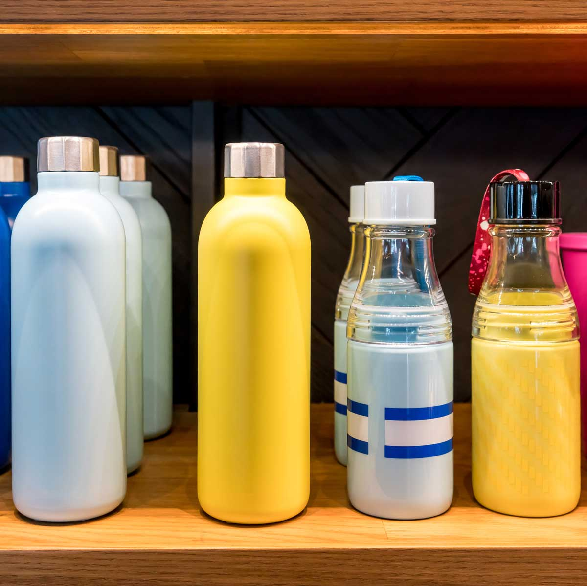 A shelf with several water bottles on it