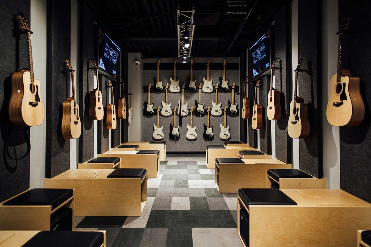 A room with heaps of electric and acoustic guitars on the wall