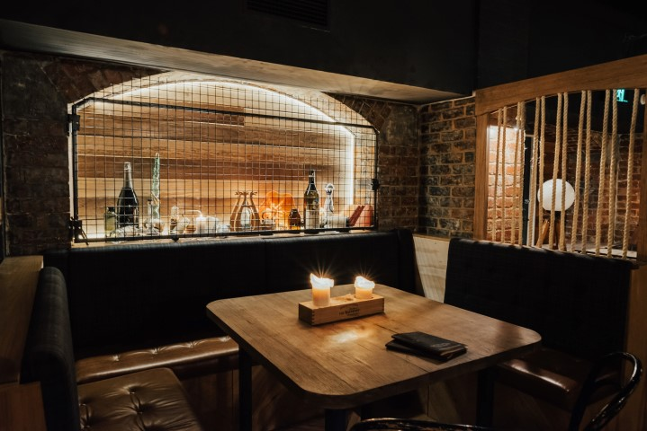 Table with candles and brick walls in a basement bar