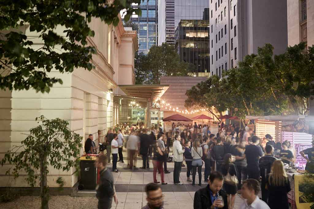 A busy outdoor courtyard with fairy lights above it