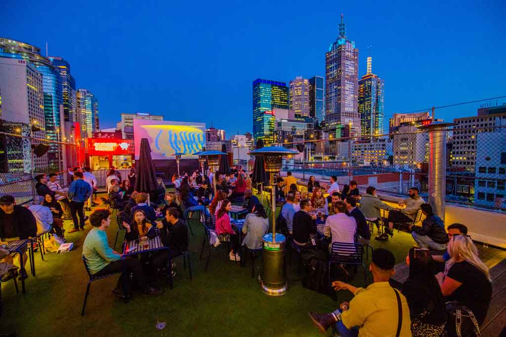 A rooftop bar with the city skyline behind it