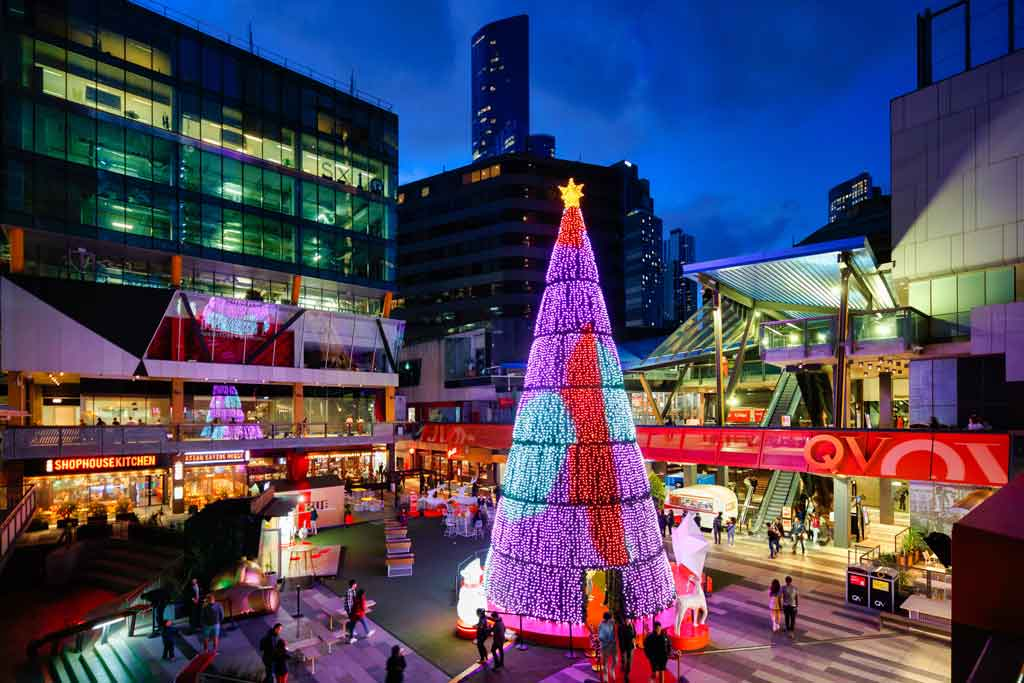 A giant glowing multi-colour Christmas tree in an outdoor chopping area
