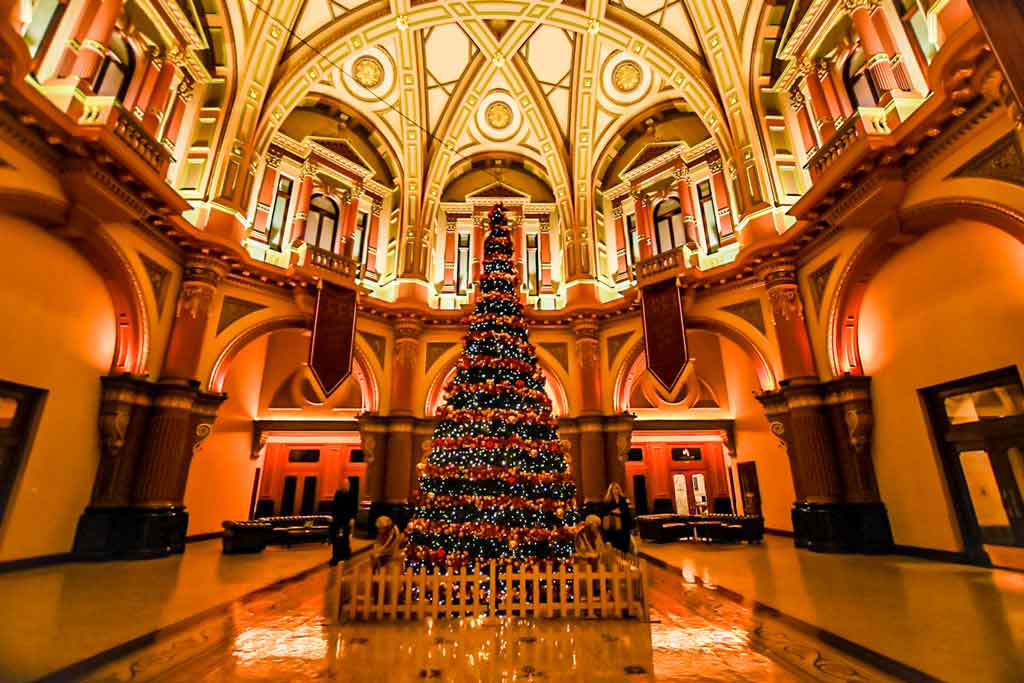 A large ornate Christmas tree in the foyer of an old building with a domed roof