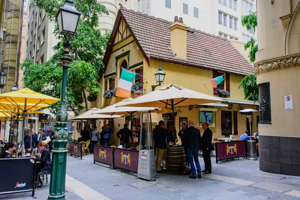 An old pub building in a laneway with people sitting outside under umbrellas
