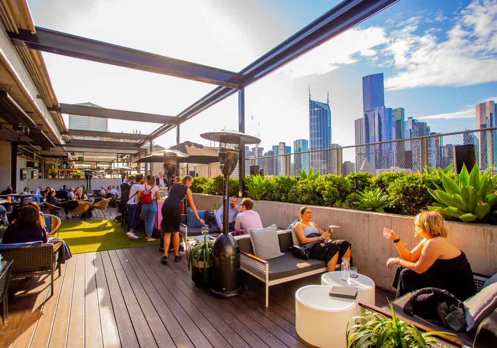 A sunny rooftop bar with wooden decking