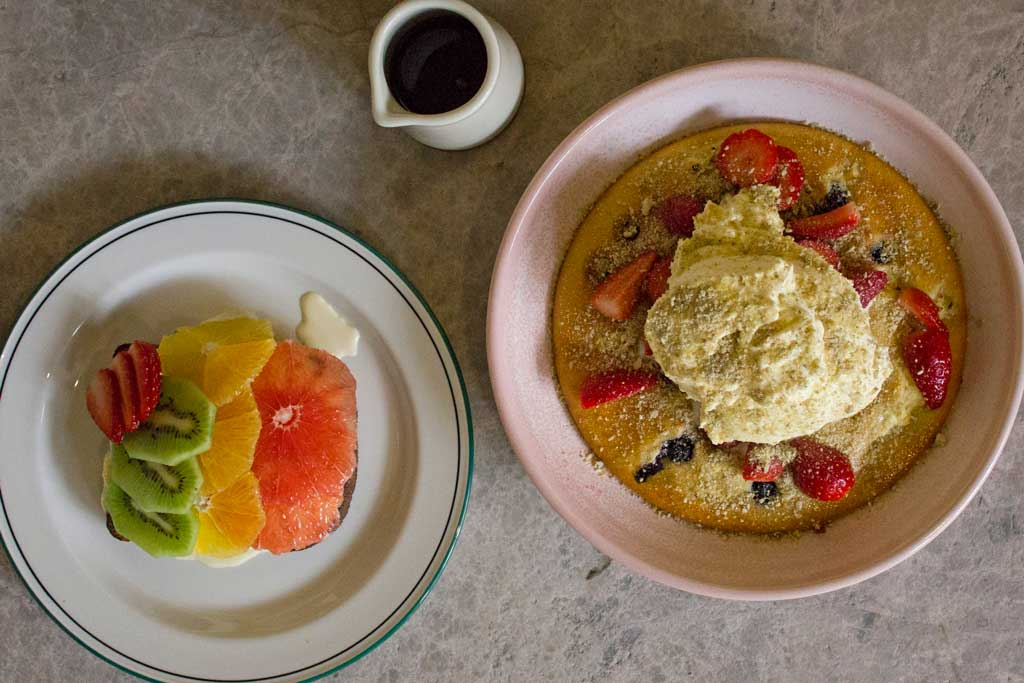 A plate of fruit and a plate of strawberry pancakes topped with cream and a jug of honey